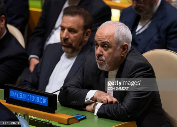Iran's Foreign Minister Mohammad Javad Zarif listens as Iran's President Hassan Rouhani speaks at the 74th session of the United Nations General...