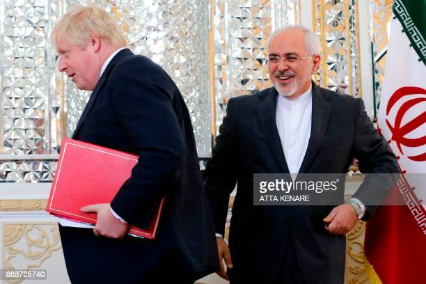 Iran's Foreign Minister Mohammad Javad Zarif shares a laugh with his British counterpart Boris Johnson during a meeting in Tehran on December 9 2017...