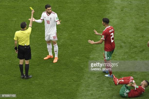 Iran's forward Alireza Jahanbakhsh reacts as he receives a yellow card from Turkish referee Cuneyt Cakir during the Russia 2018 World Cup Group B...