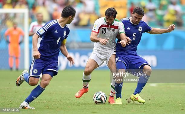 Iran's forward Karim Ansari Fard BosniaHerzegovina's defender Sead Kolasinac and BosniaHerzegovina's defender Emir Spahic vie for the ball during a...