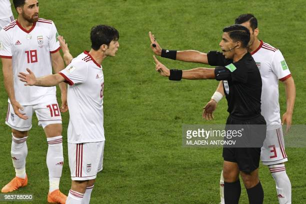 Iran's forward Sardar Azmoun argues with Paraguayan referee Enrique Caceres during the Russia 2018 World Cup Group B football match between Iran and...