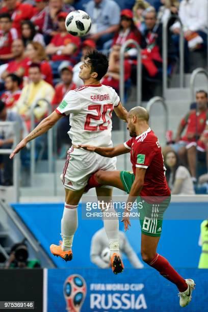 Iran's forward Sardar Azmoun heads the ball with Morocco's midfielder Karim El Ahmadi during the Russia 2018 World Cup Group B football match between...