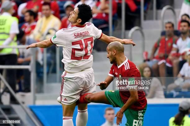 TOPSHOT Iran's forward Sardar Azmoun jumps next to Morocco's midfielder Karim El Ahmadi during the Russia 2018 World Cup Group B football match...