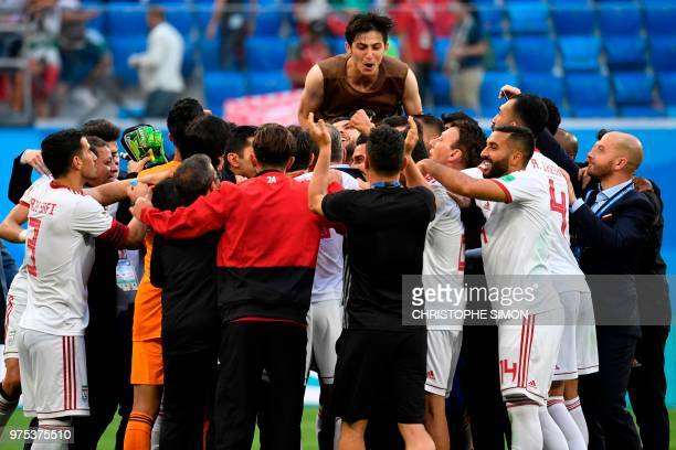 Iran's forward Sardar Azmoun jumps over teammates as they celebrate at the end of the Russia 2018 World Cup Group B football match between Morocco...