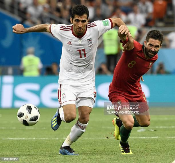 Iran's forward Vahid Amiri and Portugal's midfielder Joao Moutinho vie for the ball during the Russia 2018 World Cup Group B football match between...
