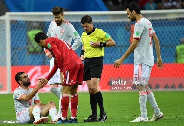 Iran's forward Vahid Amiri helps Spain's defender Dani Carvajal back to his feet during the Russia 2018 World Cup Group B football match between Iran...