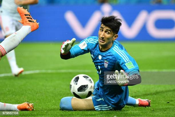 Iran's goalkeeper Alireza Beiranvand dives to save the ball during the Russia 2018 World Cup Group B football match between Iran and Spain at the...