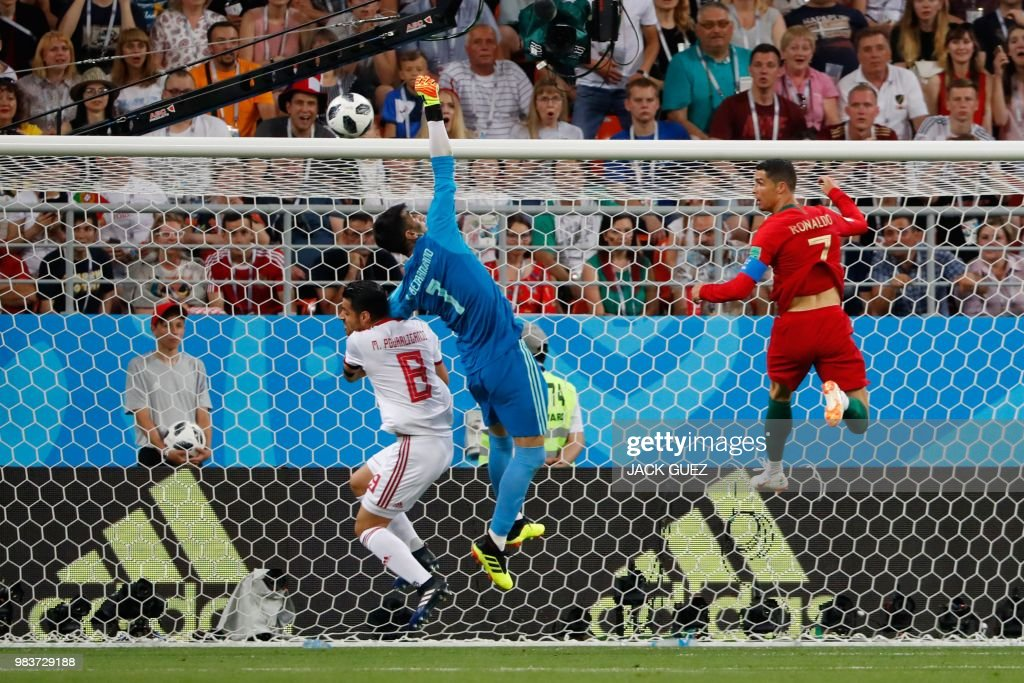 TOPSHOT - Iran's goalkeeper Alireza Beiranvand (C) jumps to save a shot during the Russia 2018 World Cup Group B football match between Iran and Portugal at the Mordovia Arena in Saransk on June 25, 2018. (Photo by Jack GUEZ / AFP) / RESTRICTED
