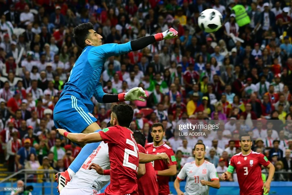 TOPSHOT - Iran's goalkeeper Alireza Beiranvand punches the ball away during the Russia 2018 World Cup Group B football match between Iran and Spain at the Kazan Arena in Kazan on June 20, 2018. (Photo by Luis Acosta / AFP) / RESTRICTED