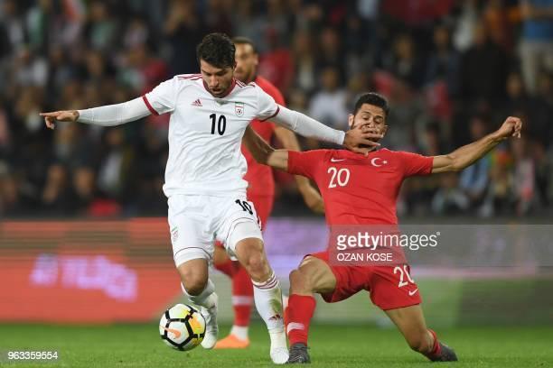 Iran's Karim Ansarifard vies for the ball with Turkey's Emre Akbaba during the friendly football match between Turkey and Iran at Basaksehir Fatih...