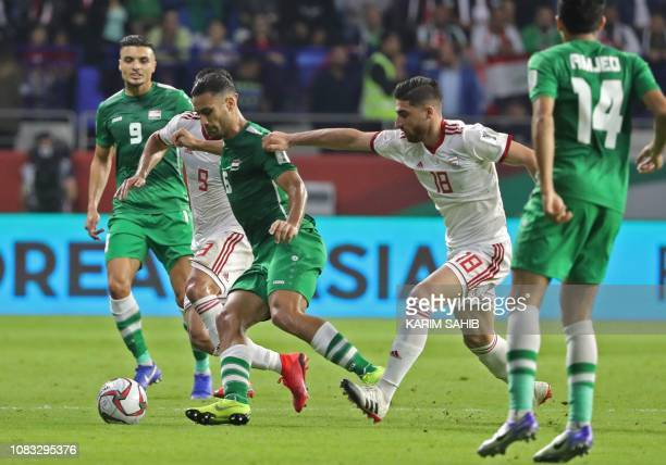 Iran's midfielder Alireza Jahanbakhsh and midfielder Omid Ebrahimi fight for the ball against Iraq's defender Ali Adnan during the 2019 AFC Asian Cup...