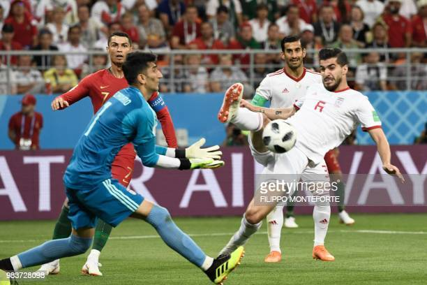 TOPSHOT Iran's midfielder Saeid Ezatolahi has a run in with his goalkeeper Alireza Beiranvand during the Russia 2018 World Cup Group B football match...