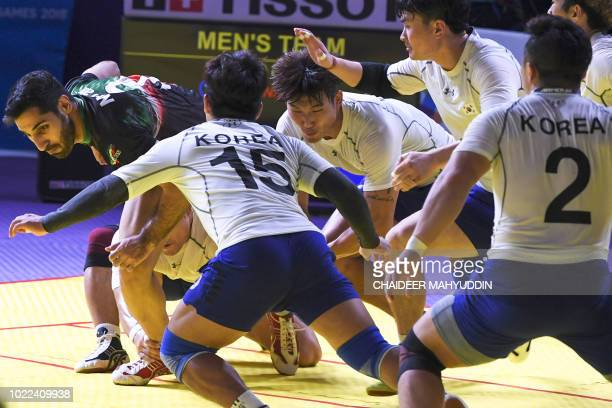 Iran's Mohammadamin Nosrati competes against South Korea's players during the of kabaddi men's team final match at the 2018 Asian Games in Jakarta on...