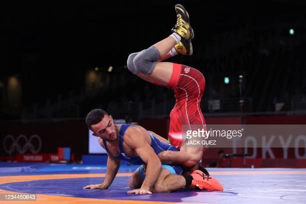 Iran's Mohammadreza Geraei wrestles Ukraine's Parviz Nasibov in their men's greco-roman 67kg wrestling final match during the Tokyo 2020 Olympic...