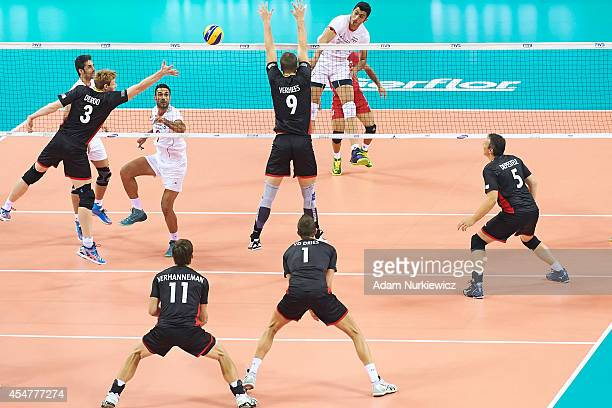 Iran's Mojtaba Mirzajanpour M. Attacks against Belgian Sam Deroo and Pieter Verhees during the FIVB World Championships match between Belgium and...