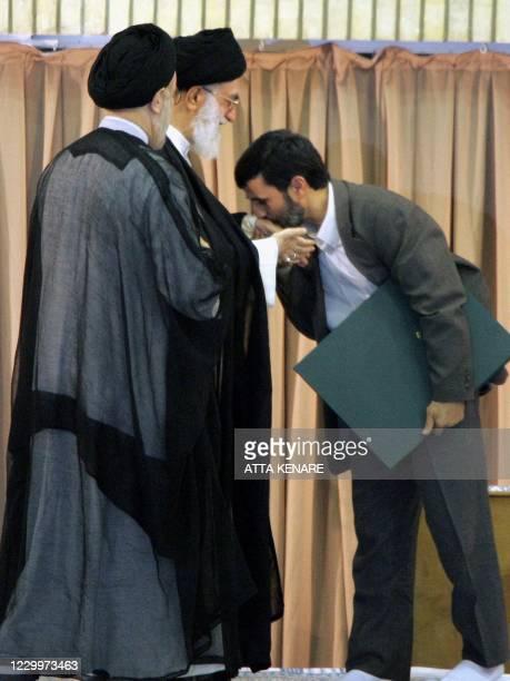 Iran's new President Mahmood Ahmadinejad kisses the hand of Iranian Supreme Leader Ayatollah Ali Khamenei during a ceremony to formally install the...