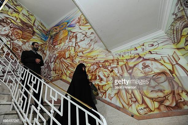 Iran's official narrator of the Den of Spies Mohammad Reza Shoghi stands beside an antiAmerican mural depicting US militarism and policy errors in...