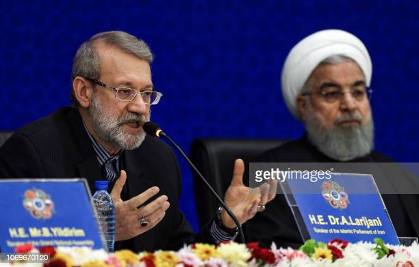 Iran's Parliament Speaker Ali Larijani speaks while seated next to President Hassan Rouhani during the 2nd Speaker's Conference which includes...