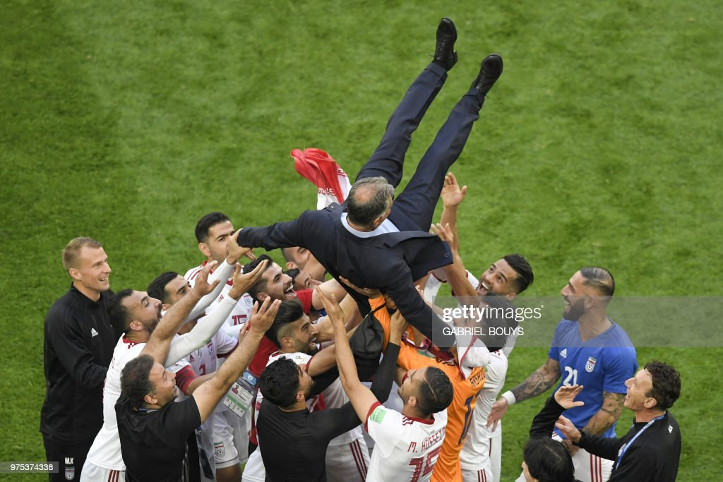 TOPSHOT - Iran's players lift their coach Carlos Queiroz as they celebrate winning the Russia 2018 World Cup Group B football match between Morocco and Iran at the Saint Petersburg Stadium in Saint Petersburg on June 15, 2018. (Photo by GABRIEL BOUYS / AFP) / RESTRICTED