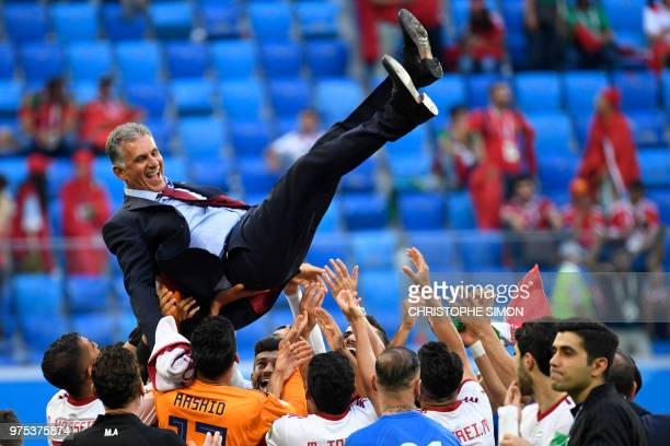 Iran's players throw coach Carlos Queiroz in the air as they celebrate at the end of the Russia 2018 World Cup Group B football match between Morocco...