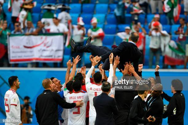 Iran's players throw Iran's coach Carlos Queiroz in the air as they celebrate after the final whistle of the Russia 2018 World Cup Group B football...