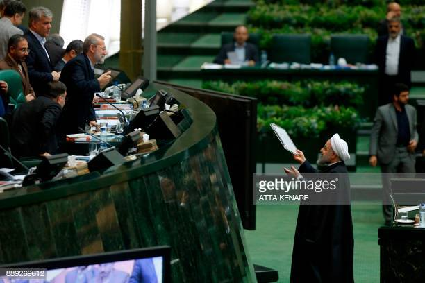 Iran's President Hassan Rouhani hands out documents to Parliament Speaker Ali Larijani after presenting his budget for 20182019 on December 10 in...