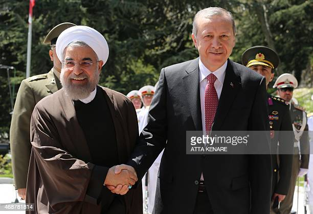 Iran's President Hassan Rouhani shakes hands with Turkish President Recep Tayyip Erdogan during an official welcoming ceremony following the latter's...