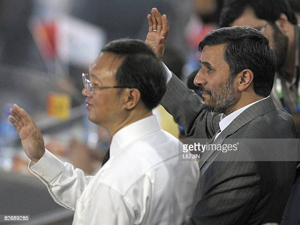 Iran's President Mahmoud Ahmadinejad and Chinese Foreign Minister Yang Jiechi wave to the Iranian delegation during the opening ceremony for the 2008...