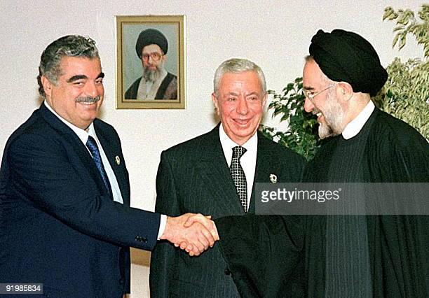Iran's President Mohammed Khatami shakes hands with Lebanese Prime Minister Rafic Hariri as Lebanese President Elias Hrawi looks on 10 December in...