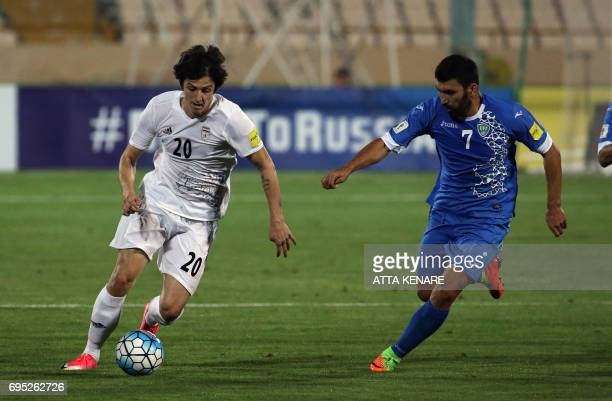 Iran's Sardar Azmoun fights for the ball against Uzbekistan's Azizbek Khaydarov during the 2018 World Cup qualifying football match between Iran and...