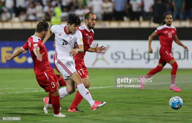 Iran's Sardar Azmoun vies for the ball against Syria's Moualad AlAjjan during the FIFA World Cup 2018 qualification football match between Iran and...