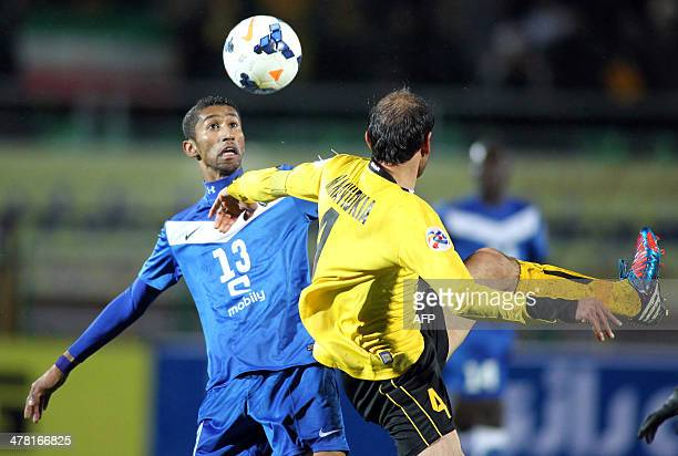 Iran's Sepahan midfielder Moharram Navidkia fights for the loose ball with Saudi Arabia's Al-Hilal midfielder Salman Al-Faraj during their AFC...