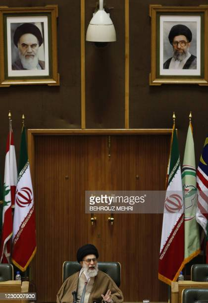 Iran's supreme leader Ayatollah Ali Khamenei delivers a speech under his portrait and a portrait of Iran's late founder of the Islamic Republic...