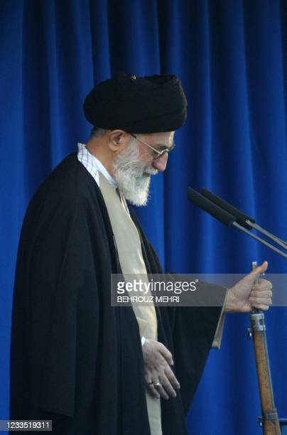 Iran's Supreme leader Ayatollah Ali Khamenei holds a rifle in his left hand as he delivers the Friday prayer sermon 14 November 2003 in Tehran's...