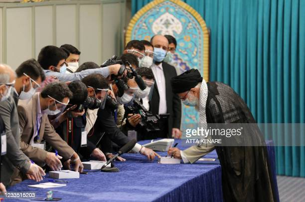 Iran's Supreme Leader Ayatollah Ali Khamenei is greeted by electoral workers, all wearing face masks due to the Covid-19 pandemic, as he arrives to...