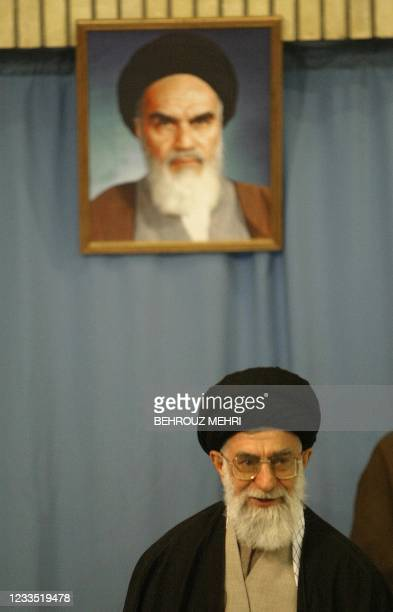 Iran's supreme leader Ayatollah Ali Khamenei votes under a portrait of Iran's late founder of the Islamic Republic, Ayatollah ruhollah Khomeini at...