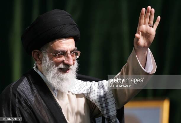 Iran's supreme leader Ayatollah Ali Khamenei waves during the 18th anniversary of the death of Iran's late fonder of the Islamic Republic Ayatollah...
