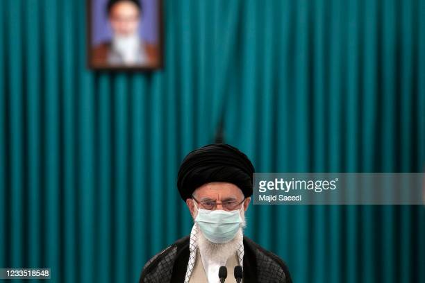 Iran's Supreme Leader Ayatollah Ali Khamenei wears a face mask due to the Covid-19 pandemic, as he arrives to cast his ballot on June 18 on the day...