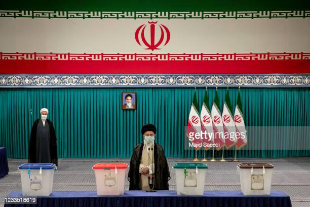 Iran's Supreme Leader Ayatollah Ali Khamenei wears a face mask due to the Covid-19 pandemic, as he stands after casting his ballot, on June 18 on the...