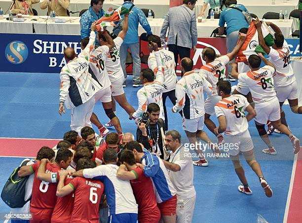 Iran's team gather as India's team celebrate victory during their men's kabaddi finals of the 17th Asian Games in Incheon on October 3 2014 AFP PHOTO...