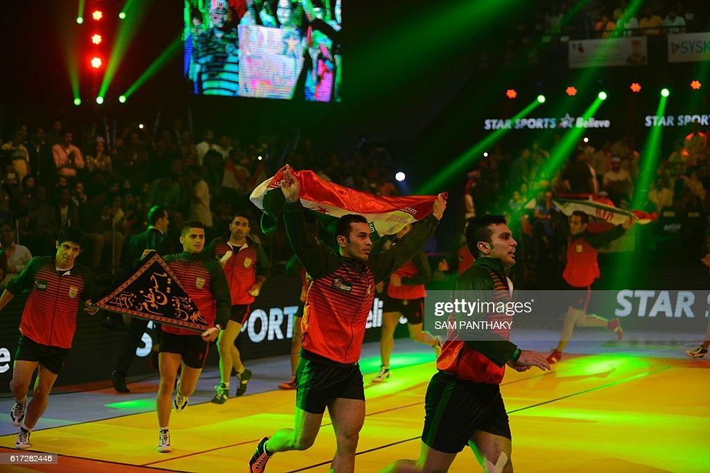 Iran's team raises the Iranian national flag as they enter the arena before Kabaddi World Cup 2016 final match against India at the Transstadia in Ahmedabad on October 22, 2016. India defeated Iran 38-29. / AFP / Sam PANTHAKY