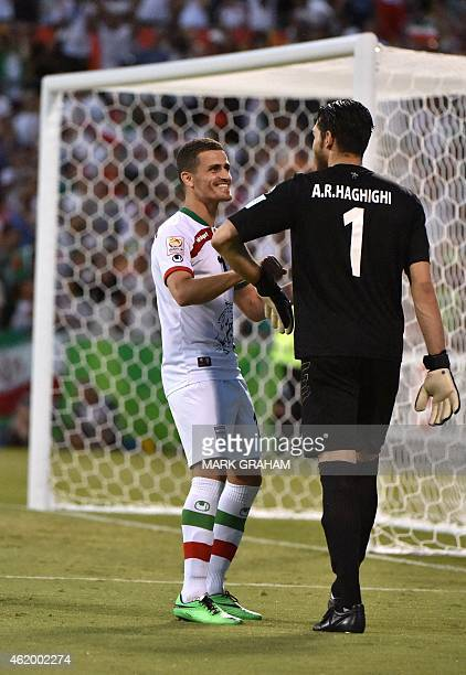 Iran's Vorya Ghafouri speaks with goalkeeper Alireza Haghighi during the Asian Cup quarterfinal football match between Iraq and Iran in Canberra on...