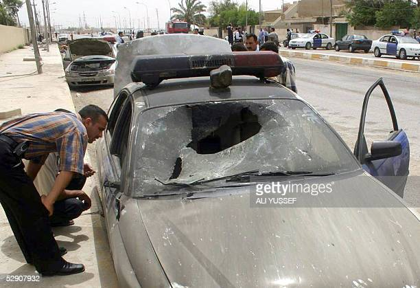 Blacked police vehicle is inspected following a car bomb in the northeastern city of Baquba, 60 kms from Baghdad 18 May 2005. Eighteen Iraqis...
