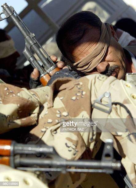 Blindfolded Iraqi detainee sits on the back of an Iraqi army truck near the Iraqi-Syrian border town of al-Qaim, in western Iraq, 26 October 2005....