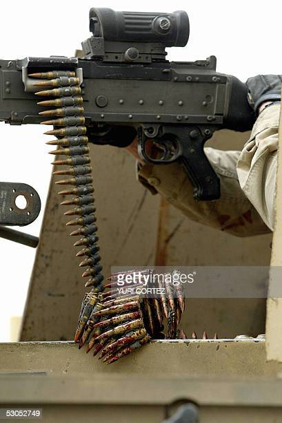 A blood stained bullet cartridge is fed into a heavy caliber machine gun a top an armoured vehicle after a US convoy was hit by a road side bomb...