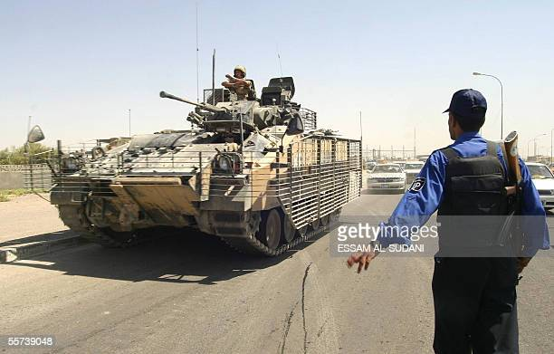 British tank drives past an Iraqi policeman in the southern Iraqi city of Basra 22 September 2005. Local authorities in southern Iraq said they will...
