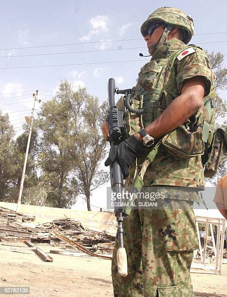 A Japanese officer secures the area as others visit a local school in the city of Samawa in southern Iraq 10 May 2005 Japan said today it would do...