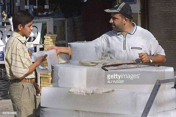 A man buys a small block of ice sold from a barrow along a street 21 July 2005 in the northeastern city of Baquba 60 kms from Baghdad The ice is sold...