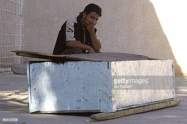 A man sits next to a coffin at the morgue at the general hospital in Baquba 60 kms northeast of Baghdad 20 August 2005 Two men were killed last night...