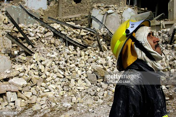 A member of Iraqi civil defense pauses as he stand over the rubble of a destroyed building at the site where two suicide bombers detonated...